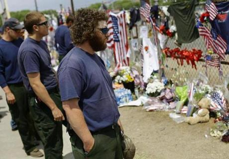 Firefighters from Idaho pay their respects at a makeshift memorial outside a fire house in Prescott, Arizona, that had been the headquarters for 19 firefighters who perished in a wildfire.