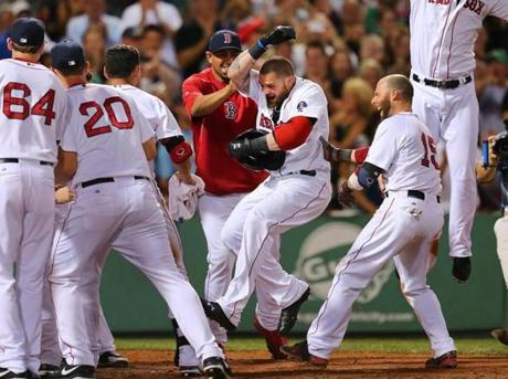 Jonny Gomes was mobbed by his Red Sox teammates at home plate after his 9th inning lead-off home run won the game against the San Diego Padres at Fenway Park.