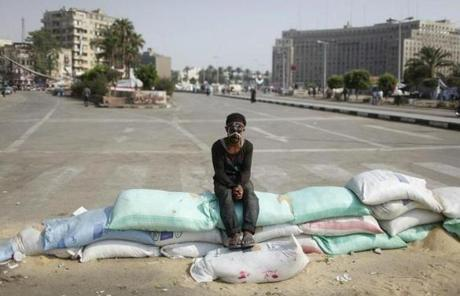 A protester, his forehead painted with the colors of the Egyptian flag, sat on sand bags used to secure the entrance of Tahrir Square.