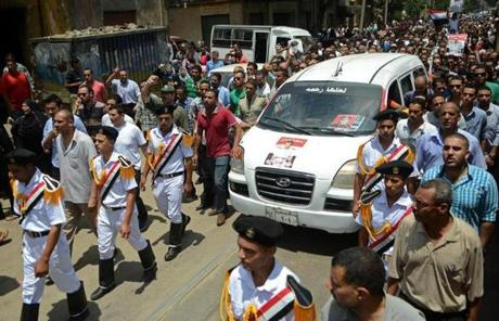 Egyptian police officers marched with a vehicle carrying the body of a comrade killed in Monday's fighting in Cairo.