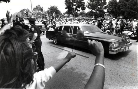 June 23 1990 / fromthearchive / Globe Staff photo by John Tlumacki / Spectators greeted the limousine carrying Nelson Mandela on Martin Luther King Boulevard. During a whirlwind tour through Roxbury and Dorchester, the Mandelas were welcomed as heroes. Thousands lined the streets and waved the ANC's black, green and gold flag. Others placed pictures of the Mandelas in their windows.