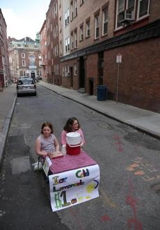 Sisters Rebecca and Brianna Woods set up their lemonade stand at Baldwin Court in the North End to wait for customers.