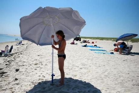 Noor van der Loo set up an umbrella at Lighthouse Beach in Chatham. Several great white sharks have been spotted near the beach this summer.