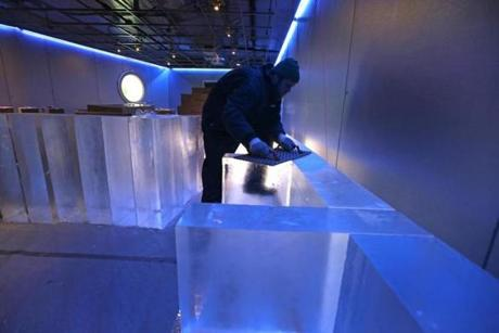 Adam Steffler worked on 300-pound blocks of ice during construction of the Frost Ice Bar at Faneuil Hall. The world's largest indoor ice bar, set to open Aug. 15, is being built by Iceculture, a company from Hensall, Ontario.