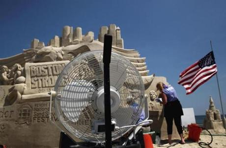 Deborah Cutulle worked on the Boston Strong centerpiece during the 10th annual Revere Beach National Sand Sculpting Festival, but her mister (foreground) temporarily stopped working.