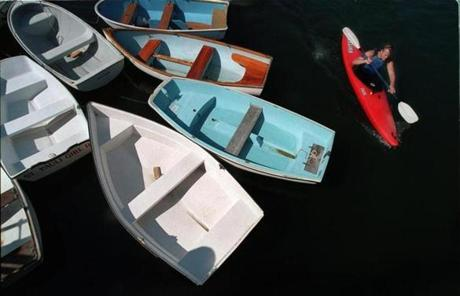 Aaron Wibbe white-water kayaked in Quissett Harbor next to dinghys tied up at the Quissett Yacht Club.