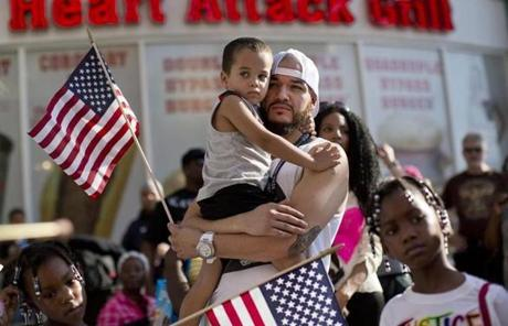 Ulysses Diaz held his son as they listened to comments before marching in a rally in Las Vegas.