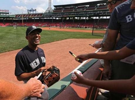 New York Yankees relief pitcher Mariano Rivera talked with fans along the left field seats before the start of a game with the Boston Red Sox at Fenway Park.