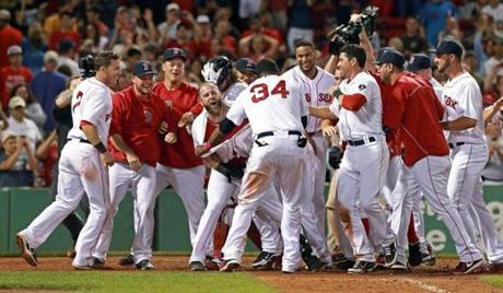 The Red Sox mobbed teammate Mike Napoli after his 11th inning walkoff  home run gave Boston a 8-7 victory over the New York Yankees at Fenway Park.