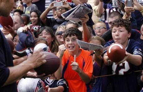 A fan reacted as Brady signed his football.