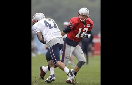 Tom Brady (right) handed off the ball to tight end Michael Hoomanawanui.