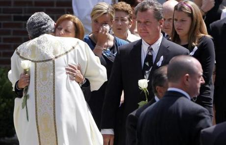 Mourners were hugged by a priest as they left St. Cecilia's Church.