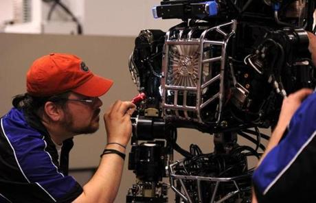 An engineer from Boston Dynamics, which built Atlas, inspects the robot.