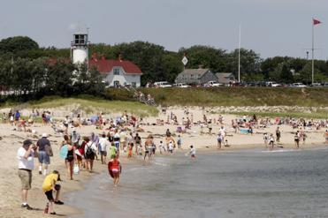 Great white sightings have not deterred visitors from the sand and surf in Chatham and elsewhere on the Cape. Here, the town's Lighthouse Beach.