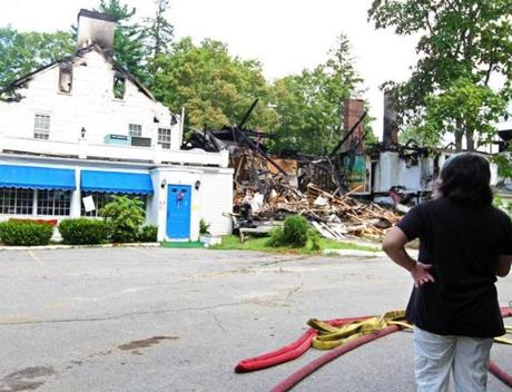 Passerby surveyed the Groton Inn after the fire.
