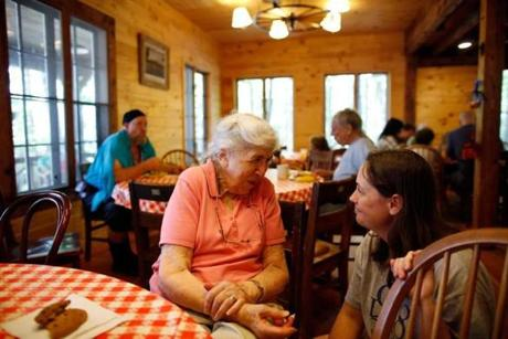 Alice Erickson chatted with Diana O'Hara of Framingham in the dining hall at Sandy Island Family Camp.
