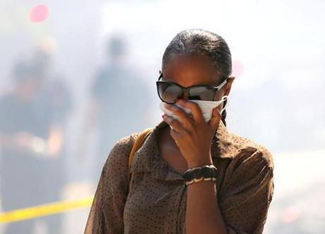 A woman covered her face while walking past the smokey fire.