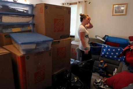 An overwhelmed Jen Regan packed the family's belongings to be moved to their new apartment, which is wheelchair accessible. She had not spent the night in their old home since the bombing, and only returned occasionally to gather some items.