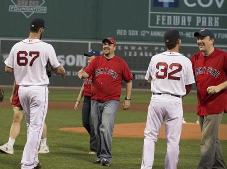 Red Sox pitchers Brandon Workman (left) and Craig Breslow greet the Collier family at Fenway Park.