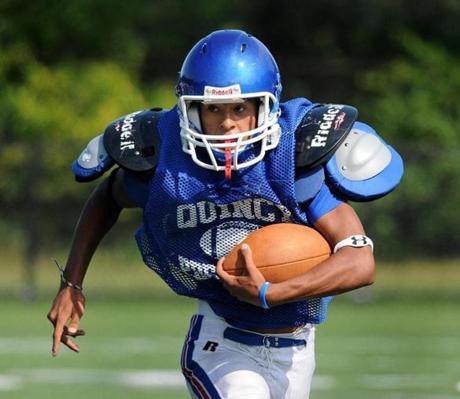 Quincy's Kenny Garcia carried the ball for a first down in the first quarter.