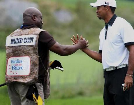 Military caddie Hardley Boswell is congratulated by Tiger Woods after sinking a putt during the pro-am.