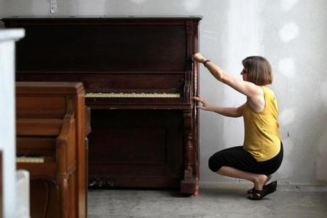 Artist Magdalena Taber takes measurements for her piano.