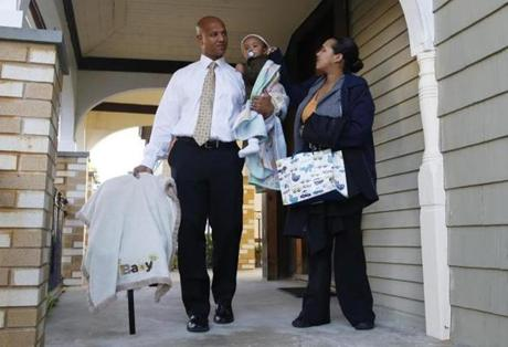 Mayoral candidate John Barros carried his sons, 16-month-old John Jr. and 1-week-old Jeremiah, as his wife, Tchintcia, reached over to fix John Jr.'s hat at their  home in Dorchester, September 19, 2013. (Jessica Rinaldi For The Boston Globe)