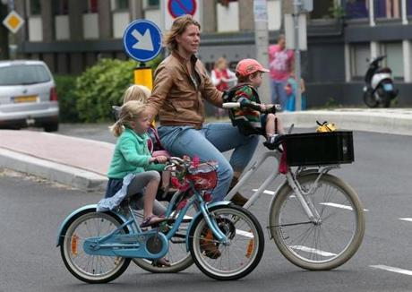In the Netherlands, almost no one rides with a helmet, and families pedal along without worry about cars.