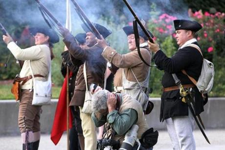 A Providence Journal photographer covered his ears as members of the End Zone Militia fired muskets.