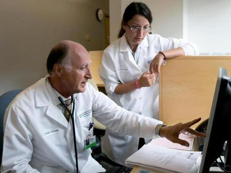 Dr. Rodney Falk checks patient data with Dr. Cristina Quarta.