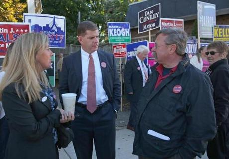 Marty Walsh, center, spoke with his friend Buddy Christopher, right. At left is his long-term friend Lorrie Higgins, outside the Rey School where Walsh voted.