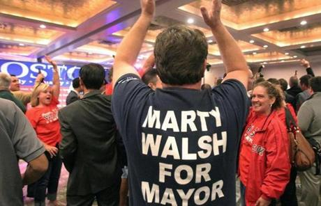 A man wearing a Martin Walsh t-shirt celebrated with other supporters.