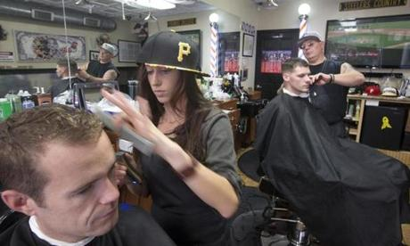 At the Southside Barber Shop Mindy Rager wore a Pirates hat as she cut the hair of (left) Ben Hodgdon, and barber R.C. Cunningham wore a Pirates hat while trimming Nick Dilanni.