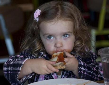 Young Sienna enjoying a Margherita pizza.