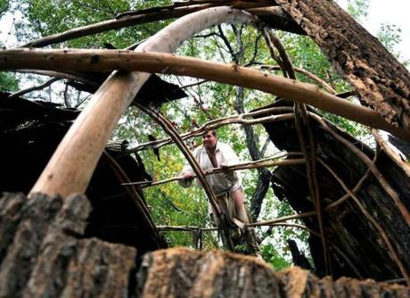 James Hakenson climbed up on one of the Wampanoag huts to remove old bark at the Plimoth Plantation.
