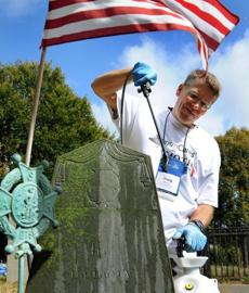 Doug Brown of Kansas City, Mo., cleans a gravestone at Burial Hill in Plymouth.