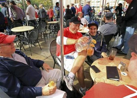 Peter Schmidt (left) flew into Boston from Bucharest to see the game with his brother, Chris, a marketing manager who called in sick from his job in Lincoln Park, N.J., and poured a drink Friday for Peter's son, Geoffrey Schmidt.