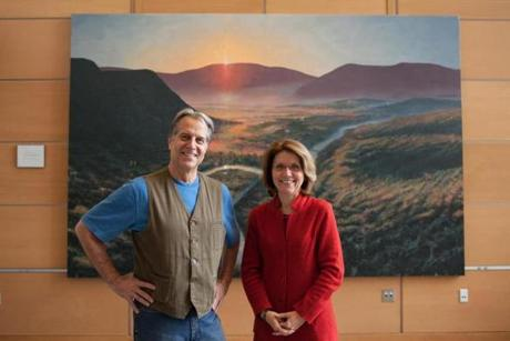 Two figures in North Adams' revival, artist Steve Hannock and Massachusetts College of Liberal Arts president Mary Grant, with his painting in the school's new science center.