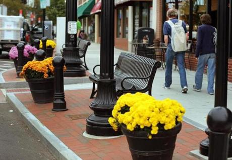 Renovations in Dedham Square include wider sidewalks — bordered with brick —  two stoplights, brick crosswalks, upgraded landscaping and benches, and a larger parking lot.