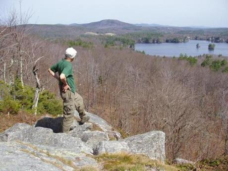 Veteran hike leader Ken Baldega, at the summit of Mount Hunger in Ashburnham, looks  across Stodges Meadow Lake to Mount Watatic.