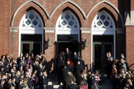 As church bells tolled, the casket was carried up the steep stone steps into the church.