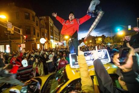 Fans celebrated by jumping on a moving cab on Massachusetts Avenue and Boylston Street in Boston.