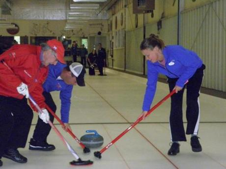 Sweepers at the Cape Cod Curling Club help control the stone's speed as it slides down the ice.
