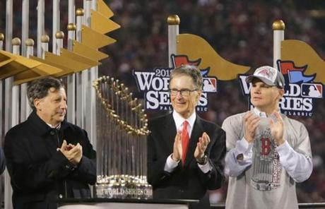 Team chairmanTom Werner, principal owner John Henry, and general manager Ben Cherington are seen with the trophy.
