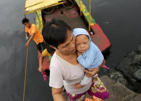 Ahead of the storm's landfall, a resident carried a baby as they crossed a river.
