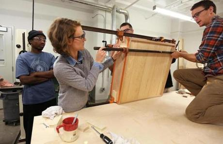 Crockett (left) watched a demonstration of work on a wall cabinet by Stewart Pugsley, John D'Anna, and Sam Holcomb.