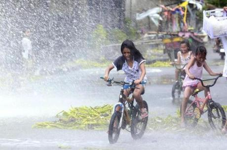 Girls riding on bicycles were splashed by strong waves in a coastal village as Haiyan battered Bayog town.