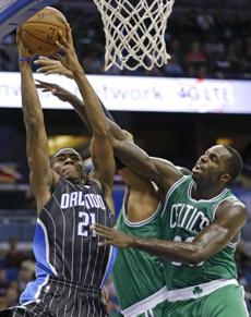 Orlando Magic's Maurice Harkless (21) gets up over Boston Celtics' Jared Sullinger, center, and Brandon Bass, right, for a shot during the second half of an NBA basketball game in Orlando, Fla., Friday, Nov. 8, 2013. (AP Photo/John Raoux)