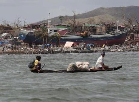 A ship washed ashore near damaged houses in Tacloban.