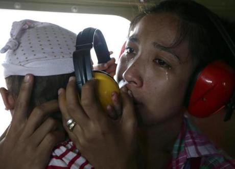 A mother cried after boarding a Philippine Air Force helicopter Monday in Guiuan.
